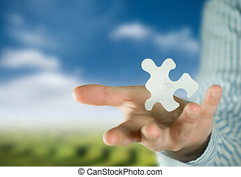 Puzzle and Solution - A man holding a puzzle piece