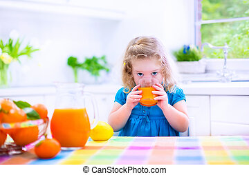Little girl drinking orange juice - Cute funny little girl...