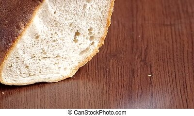 Slicing bread with a knife on a wooden table