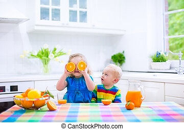 Kids drinking orange juice - Cute funny little girl and...