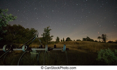Night Time Lapse of stars, field tools and thistle -...