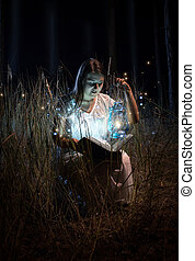 smiling woman in nightgown sitting at field at night and...