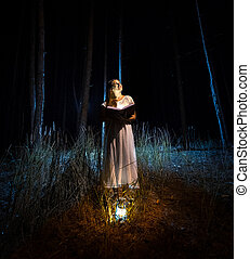 Mysterious shot of woman reading big book at dark forest -...