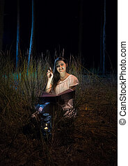 photo of smiling woman holding book at beautiful night...