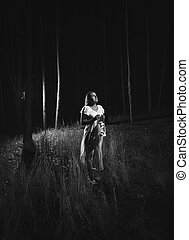 Monochrome photo of woman in white dress walking at forest...