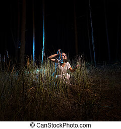 woman in nightgown sitting in high forest at night with...
