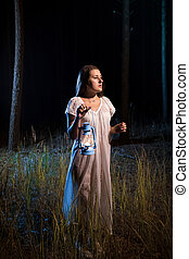 lost woman in forest at night walking with candle lantern -...