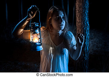 portrait of scared woman lost in forest lighting up the way...