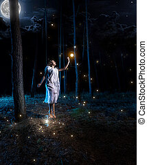 young woman at night forest with full moon jumping high to...
