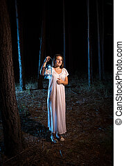 young woman in nightgown walking in forest at night with gas...