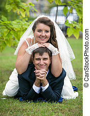 outdoor portrait of bride lying on grooms back on grass at...