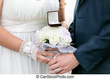 bride and groom holding wedding bouquet with golden rings -...