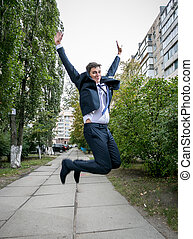 excited businessman in suit jumping on street - Outdoor shot...