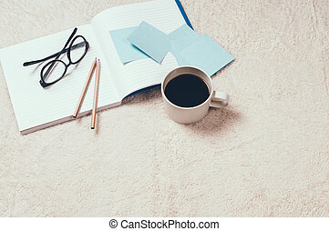 Home study: Notebooks, coffee and glasses on the floor,...