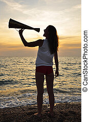 girl shouting into a megaphone at sea