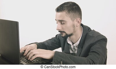 Sleepy businessman typing at his desk