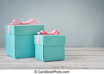 Blue polka dots gift boxes with pink ribbons on wooden...