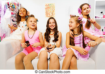 Happy girls with hair-curlers sit on white sofa - Happy...