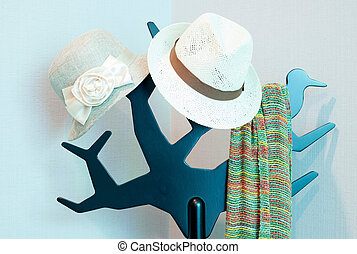 Bright colored scarf with hat hanging on a rack in a...
