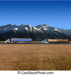 Two Trucks on Highway with Mountains