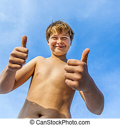 happy smiling young boy gives fingersign thumbs-up - happy...