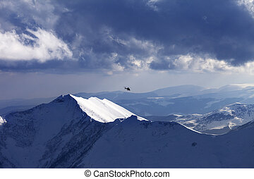 Off-piste slope for heliskiing and helicopter in evening....