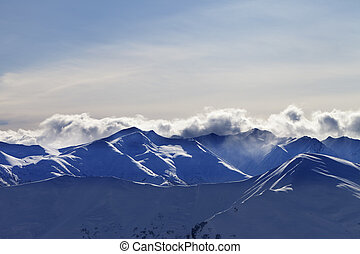 Evening winter mountains and sunlight clouds. Caucasus...