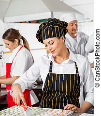 Female Chef Cutting Ravioli Pasta With Colleagues In...