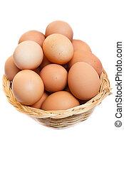 Eggs in wicker basket - fresh raw brown eggs in a basket