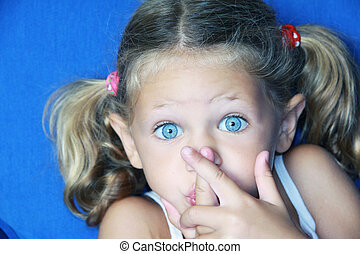 quiet please - a young caucasian child with her hands to her...