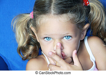quiet please - a young caucasian child making a gesture with...