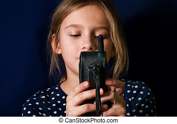 Girl with Mobile Phone - Close up of a young girl holding...