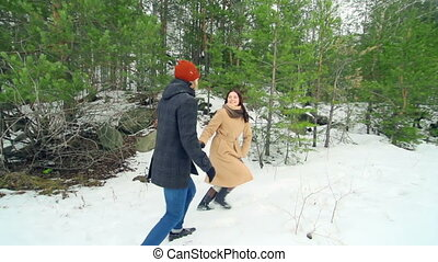 Snowball Fight - Cheerful couple enjoying their winter...