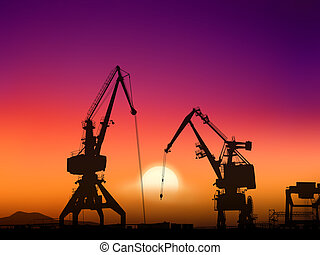 sunset - Two cranes sit dramatically against a colorful...