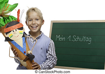 Child standing beside chalkboard and smiles happy