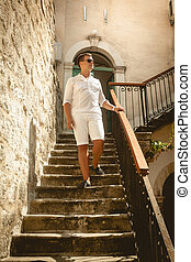 man walking down the old stone staircase at sunny day -...