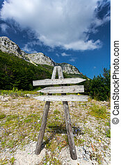 wooden signpost on path to high mountain - Blank wooden...
