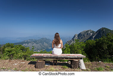 brunette woman sitting on bench at high mountain - Beautiful...