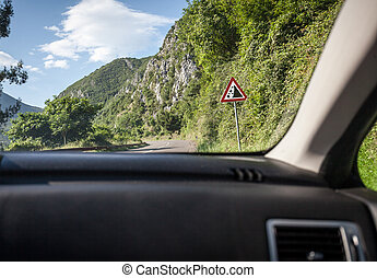 View on warning of landslide sign on road from inside of car...