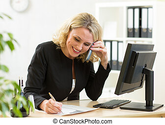 Smiling middle-aged business woman working in office