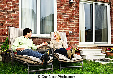 Happy couple relaxing at home - Happy couple in backyard of...