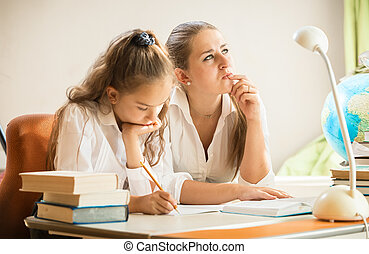 mother trying to solve complicated exercise with little...