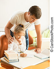 young father looking at daughter doing homework