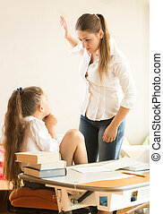 angry mother hitting intimidated daughter - Portrait of...