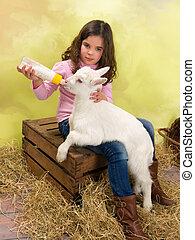 Girl feeding baby goat