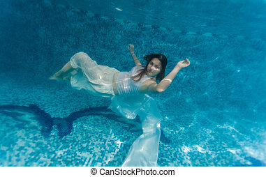 woman in white cloth swimming underwater - Underwater shot...