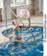 beautiful young woman playing with beach ball at swimming...