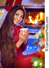 Beautiful smiling girl by the Christmas fireplace. Woman...