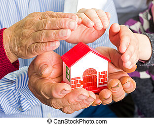 Home insurance - Photo of a miniature house holding in hands