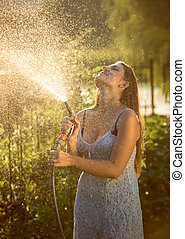 young woman watering garden with hose pipe - Beautiful young...